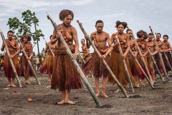 Young boys and girls, painted in bright orange colours and singing traditional songs, at Gulf Mask Festival in Gulf province in Papua New Guinea