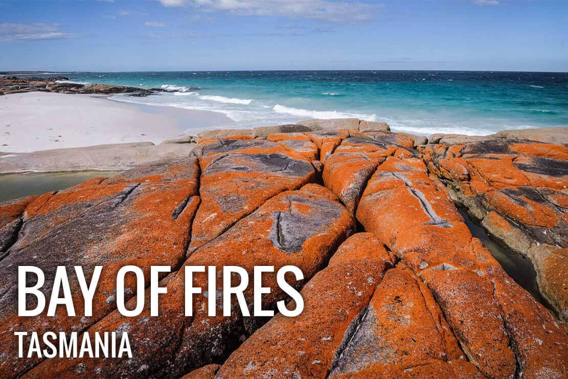 Walking in Bay of Fires in Tasmania, with its endless white sandy beaches, crystal clear azure waters and boulders draped in bright orange lichen