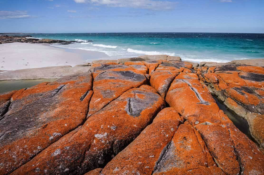 Walking along endless powder-white sandy beaches of Bay of Fires in Tasmania punctuated by lagoons, rocky formations and coastal bush