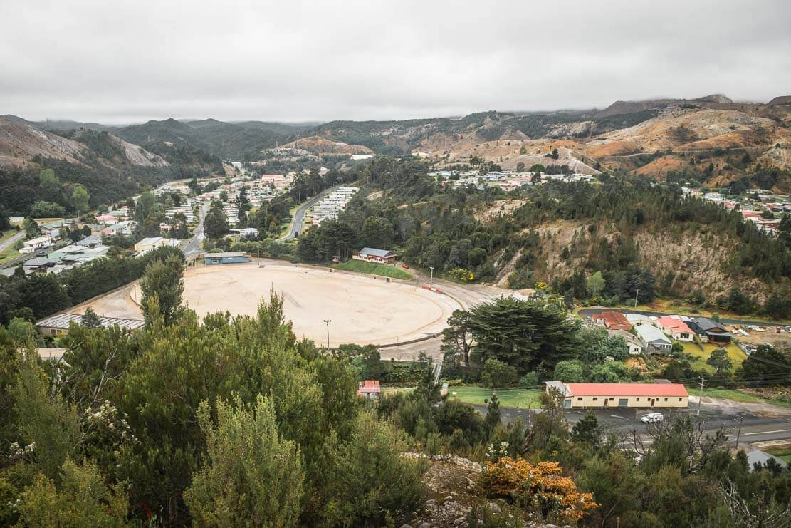 Heritage listed gravel-surfaced football oval viewed from Spion Kop Lookout in Queenstown on the West Coast of Tasmania