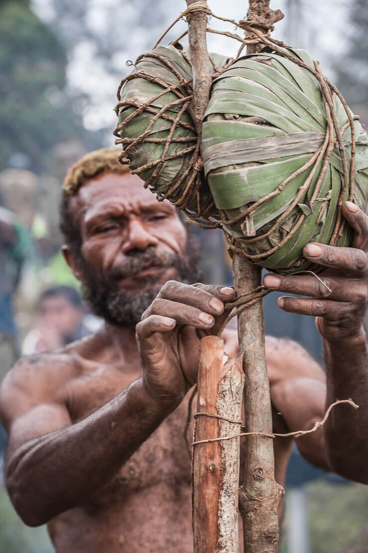 Marcus, a traditional salt maker with Enga salt wrapped in leaves and attached to a wooden stick for the ease of transportation